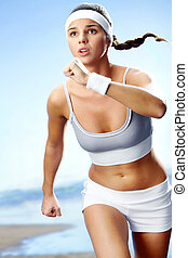Young runner - Portrait of a girl running against beach...