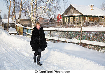 Young russian woman at winter in the snowy village.