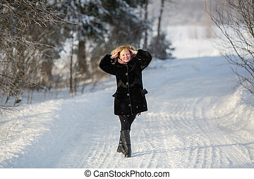Young russian woman at winter on the snowy road in village.