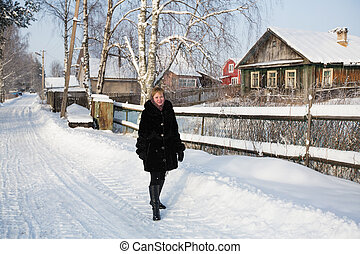 Young russian woman in the village at winter.