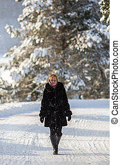 Young russian woman standing in the winter on a snowy road.