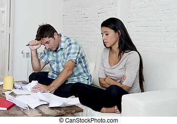 young sad couple at home living room couch calculating monthly expenses worried in stress
