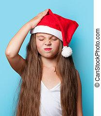 Young sad girl in Santas hat
