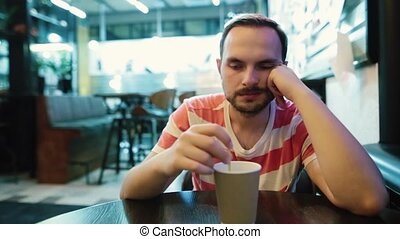 Young, sad man waiting for someone in cafe in the city.