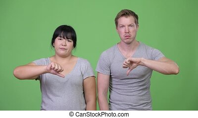 Young sad multi-ethnic couple giving thumbs down together