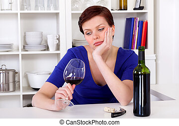 young sad thinkful woman drinking a glass of red wine -...