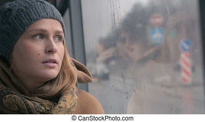 Young sad woman in the bus on a dull rainy day