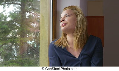 Young sad woman looking out the window and waiting