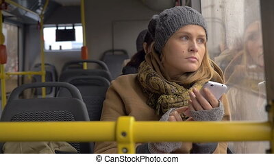 Young sad woman using smart phone in the bus