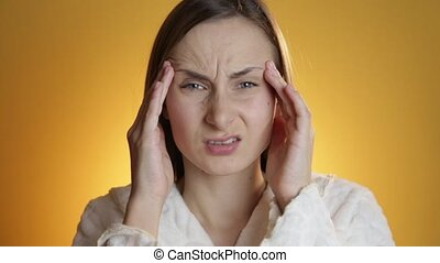 Young sad woman with headache massaging her temples with circular motion, healthcare and stress concept.