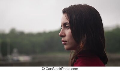 Young sad woman with wet hair looking away, cloudy rainy...