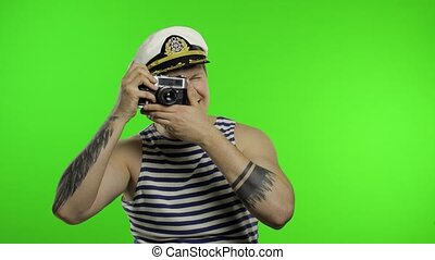 Young sailor man takes a photo on a retro camera. Seaman guy in sailor's vest