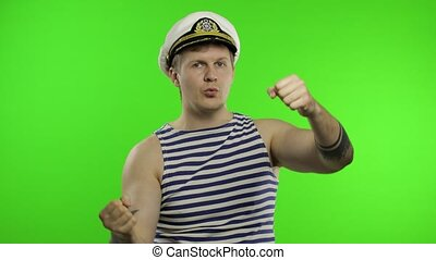 Young muscular sailor man with imaginary wheel of the ship. Seaman guy smiling in sailor's vest. Striped navy white and blue shirt, captain nautical hat. Isolated on chroma key background
