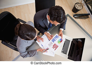 Young sales persons studying statistics in an office