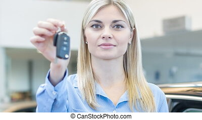 Young saleswoman is upholding the car keys.