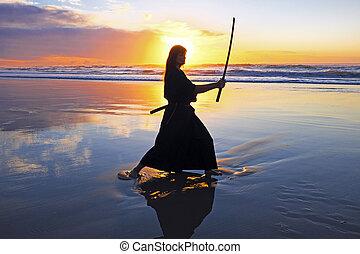 Young samurai women with Japanese sword(Katana) at sunset on...