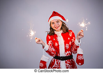 Young santa claus woman in red christmas or new year coat and hat holding sparkler and bengal fire.