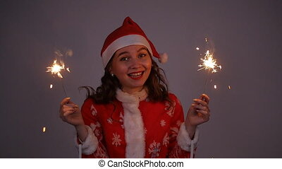 Young santa claus woman in red christmas or new year coat and hat holding sparkler