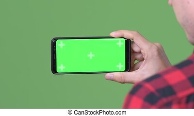 Young Scandinavian businessman using mobile phone against green background