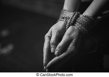 Tight knit. Powerless weak desperate woman having her hands hindered with ropes while being taken hostage and sitting somewhere dark