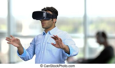 Young scared man wearing virtual reality glasses. Indian man with VR goggles experiencing VR game. Blurred office background.