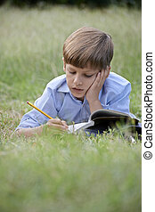 Young school boy doing homework alone, lying on grass