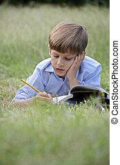 Young school boy doing homework alone, lying on grass