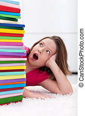 Young school girl shocked by the large stack of books