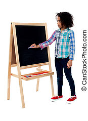 Young school girl writing on blackboard