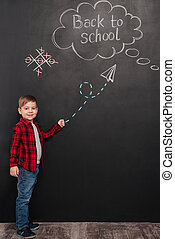 Young schoolboy over background of chalkboard pointing on school drawings