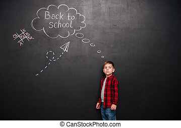 Young schoolboy standing over background of chalkboard with school drawings