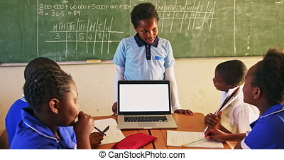 Young schoolboy with laptop at the front of class 4k