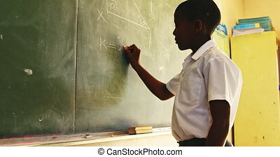 Young schoolboy writing on the blackboard in class 4k