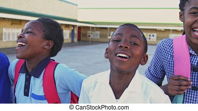 Panning portrait close up of young African schoolchildren wearing school uniforms and schoolbags, looking to camera smiling in the playground at a township elementary school 4k