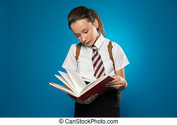 Young schoolgirl reading from a class text book - Young...
