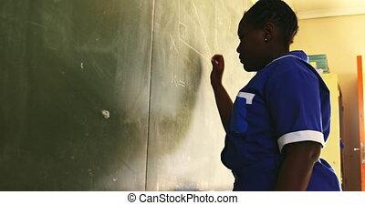 Young schoolgirl writing on the blackboard in class 4k