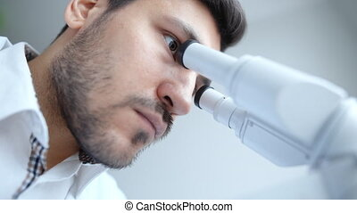 Young scientist looking through microscope