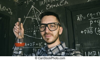 Young scientist man making selfie shoot in chemical and mathematical equations wall room interior