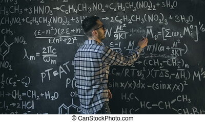 Young scientist man write chock in chemical and mathematical equations wall room interior