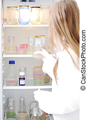 Young scientist opening refrigerator in the lab
