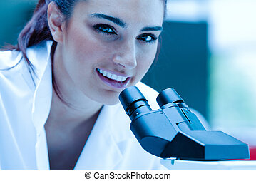 Young scientist posing with a microscope
