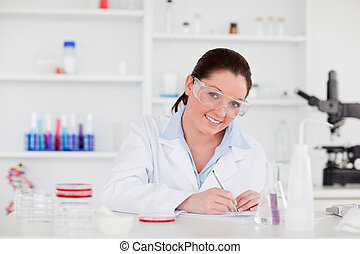 Young scientist preparing  her report looking at the camera