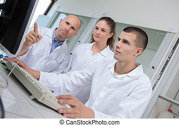 Young scientist working on computer, teacher pointing to screen
