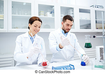 young scientists making test or research in lab - science,...
