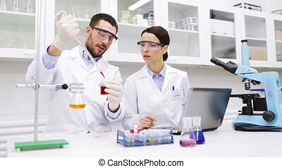 science, chemistry, technology, biology and people concept - young scientists with pipette and glass making test or research in clinical laboratory