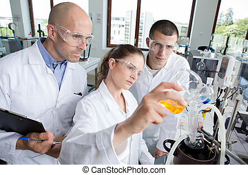 young scientists wearing protective glasses in clinical...