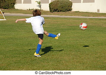 Young scoccer player training