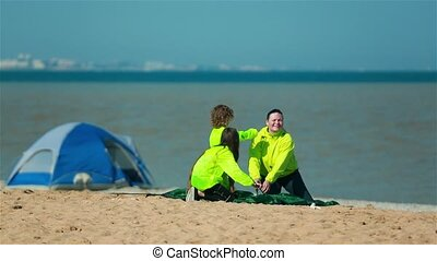 Young scouts and the coach set a tent on the shore of the lake.