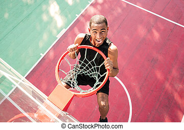 Young screaming african basketball player practicing