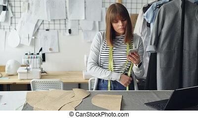 Young seamstress is checking clothing paper patterns and...